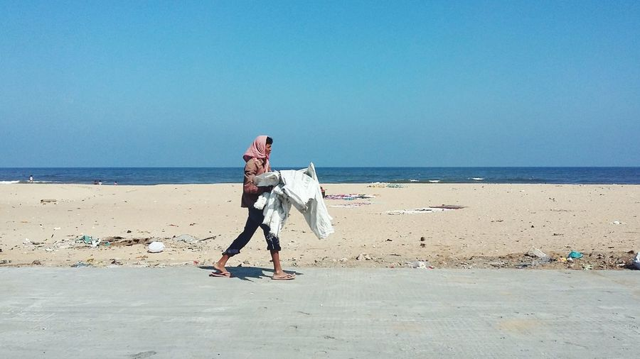 Side view of man holding sack while walking at beach against clear blue sky