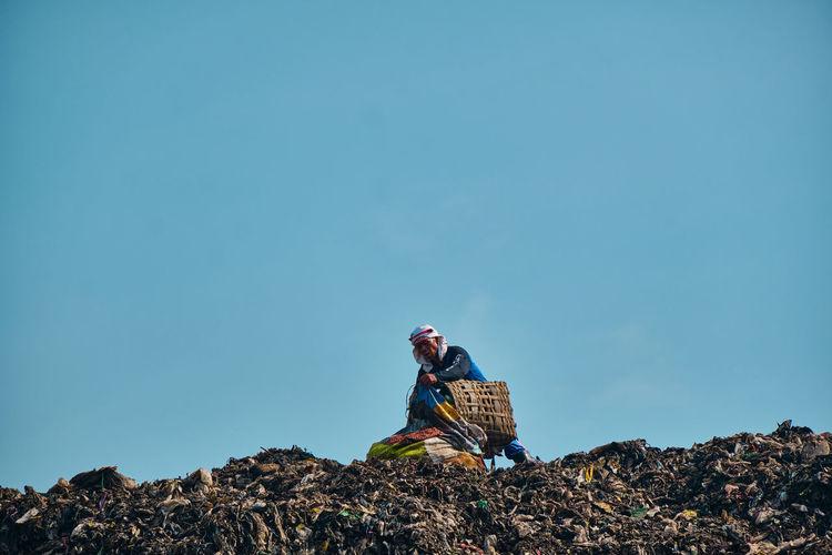 Man sitting on rock against clear sky