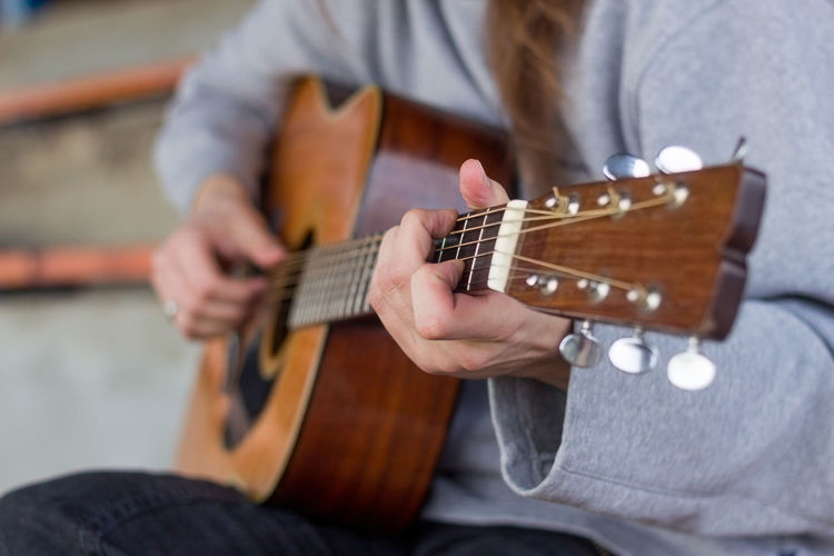 Arts Culture And Entertainment Casual Clothing Classical Guitar Close-up Day Fretboard Guitar Holding Human Hand Indoors  Leisure Activity Lifestyles Men Midsection Music Musical Instrument Musical Instrument String Musician One Person Playing Plucking An Instrument Real People Sitting Skill  String Instrument