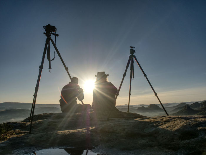 Creative artists stay at own cameras on tripods. photo enthusiasts work together on cliff