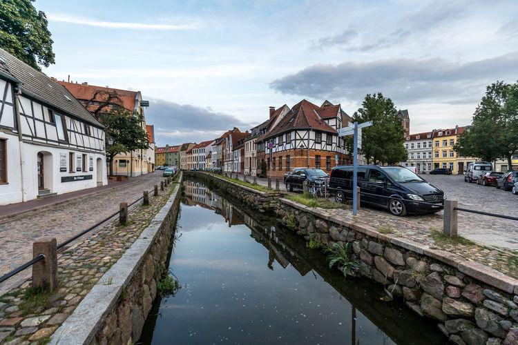 Canal amidst buildings against sky