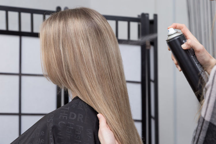 Cropped hand of hairdresser holding woman hair at salon