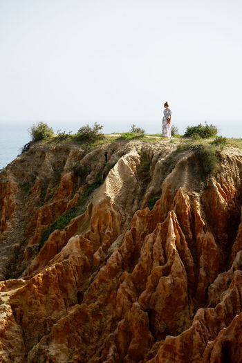 Woman standing on cliff against clear sky