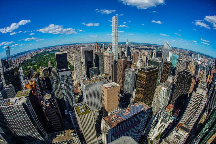 Aerial view of modern buildings against cloudy sky