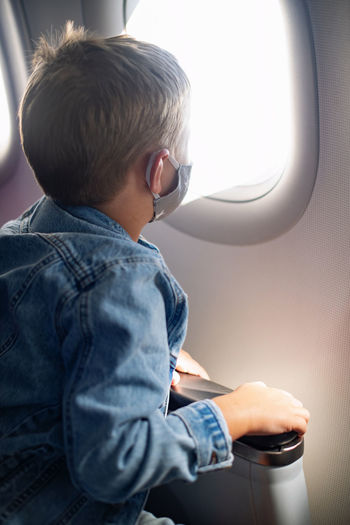 Rear view of boy sitting in airplane