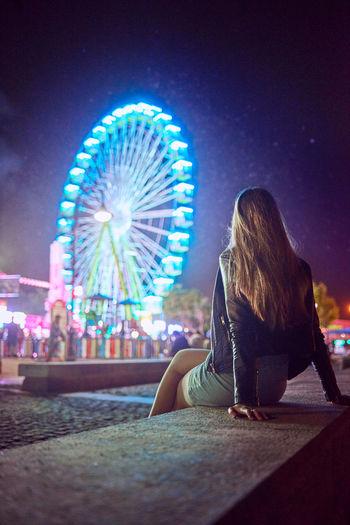 Illuminated ferris wheel against sky in city at night