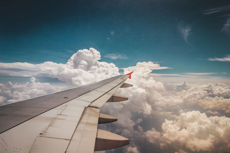 Cropped image of airplane wing flying against sky