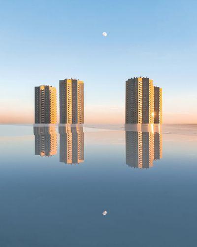 Digital composite image of modern buildings by sea against sky