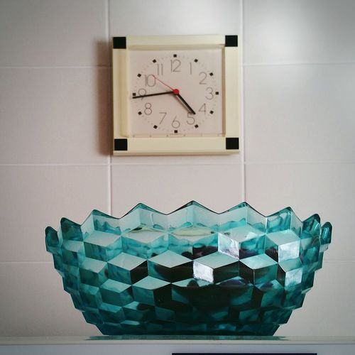 Close-up of clock on table against wall