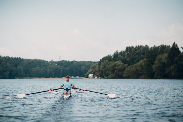 Man rowing canoe in lake