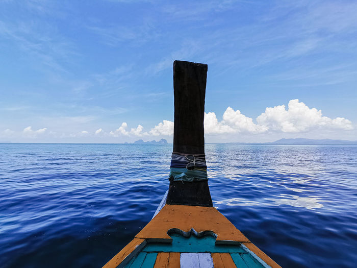 Wooden boat in sea against sky