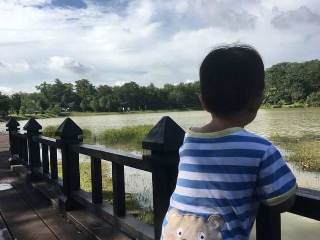 Real People Sky Tree Cloud - Sky Leisure Activity Nature Day Casual Clothing Outdoors Rear View Childhood One Person Boys Lifestyles River Beauty In Nature Growth Water Standing Scenics
