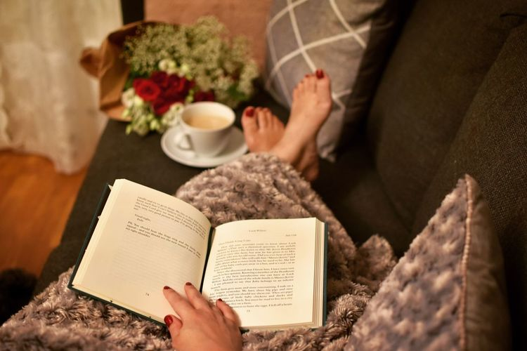 Read me... At Home Sofa Books Coffee Flowers Human Hand Human Body Part Indoors  Hand One Person Publication Book Adult Women Lifestyles Reading Leisure Activity Real People High Angle View