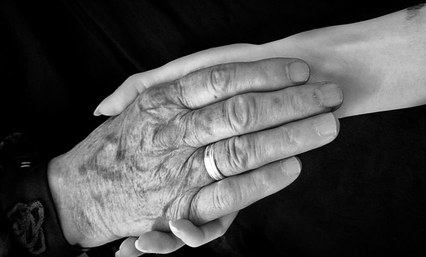 Close-up of woman holding hands against black background