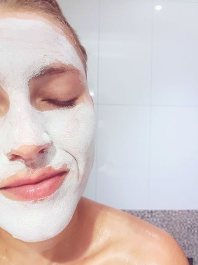 Close-up of woman with eyes closed and facial mask in bathroom
