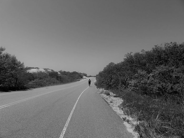 Rear view of person riding bicycle on road against clear sky