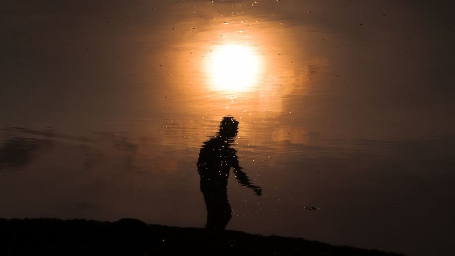 Silhouette man standing in water against sky during sunset
