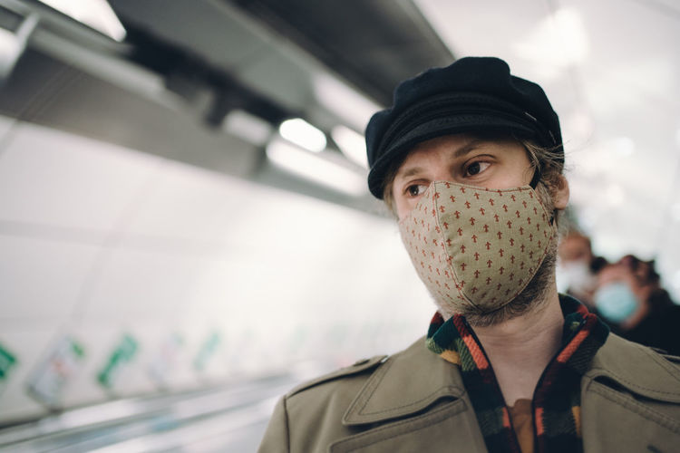 Man going down the escalators in the underground wearing a face mask