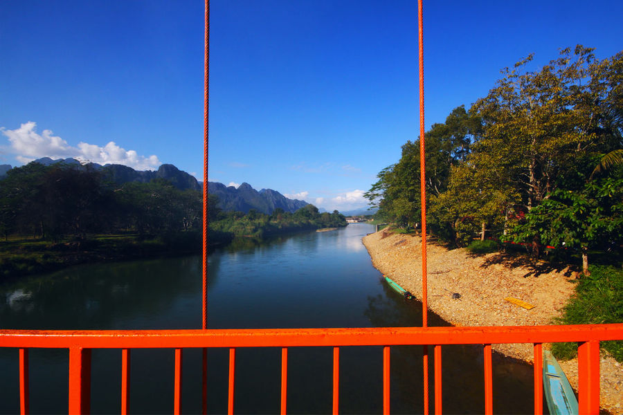 Orange steel bridge across on the river and mountain at countryside of Vangvieng, Laos Vangvieng,Laos Architecture Beauty In Nature Countryside Day Idyllic Lake Mountain Mountains Nature No People Non-urban Scene Outdoors Plant Railing Scenics - Nature Sky Steel Bridge Tranquil Scene Tranquility Tree Water
