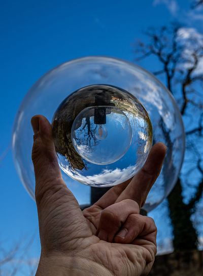 Close-up of hand holding glass against blue sky