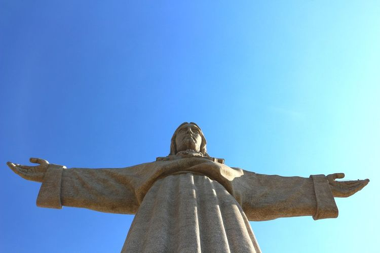 Low angle view of jesus christ statue against blue sky