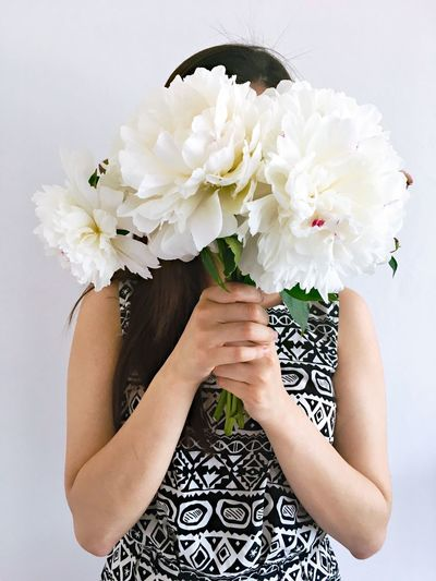 Close-up of woman holding white flower