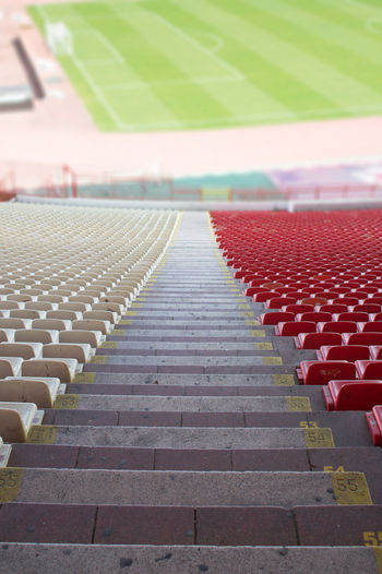 red and white seats at the stadium Empty In A Row Seat Absence Stadium No People Sport Staircase Chair Architecture Day Repetition Outdoors Red Large Group Of Objects Vertical Seats Plastic Detail Soccer Football Event Public Game Team