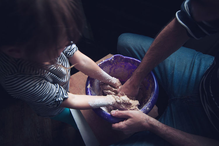 High angle view of father and daughter making dough in container on table