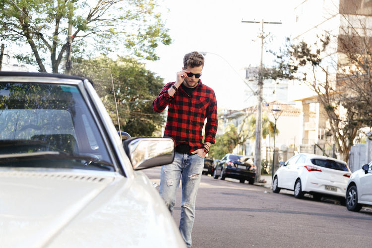 Car Casual Clothing Day Front View Land Vehicle Lifestyles Mode Of Transport One Person Outdoors People Real People Road Standing Transportation Tree Vehicle Breakdown Young Adult
