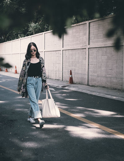 Full length of young woman with shopping bag walking on road