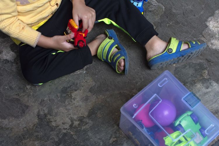 Bandung Shooter Indonesian Shooter Adult Body Part Casual Clothing Hand High Angle View Holding Human Body Part Human Leg Leisure Activity Lifestyles Low Section Men Multi Colored One Person Playing Real People Shoe Sitting Toy Women