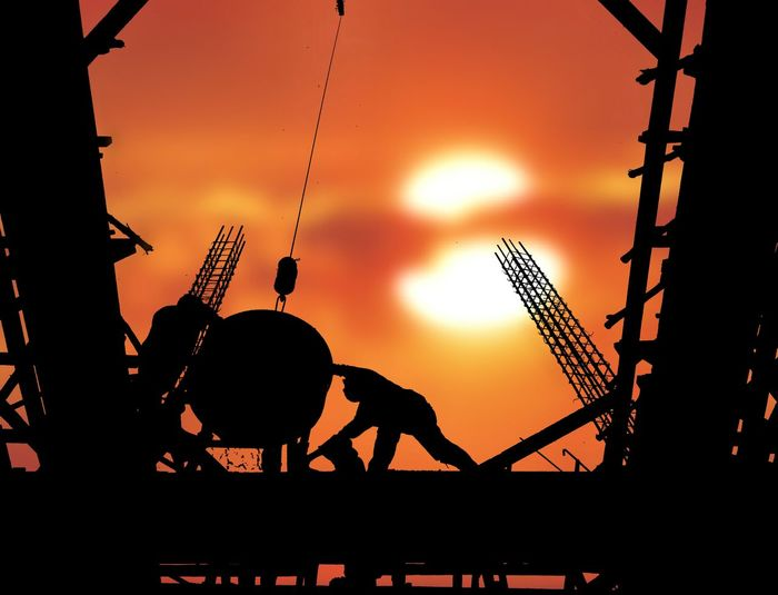 Silhouette construction workers are casting concrete on top of building structure with blurred sundown sky background on occupation concept Construction Workers Casting Concrete Top Of Building Structure Blur Background Sundown Sunset Morning Evening Reinforcement Technology Development Occupation Site Low Angle View Shadow Silhouette Outdoors Sunset Silhouette Metal Industry Occupation Sky