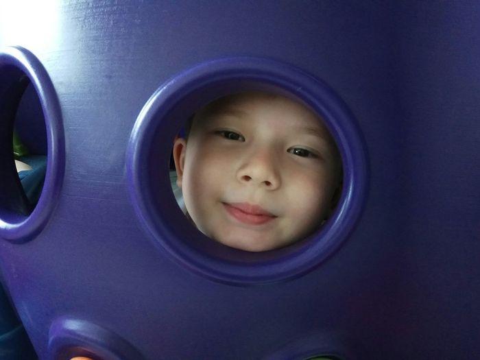 Portrait of cute boy seen through hole