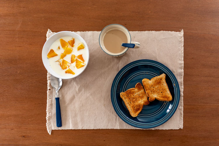 Healthy breakfast with orange, coffee and toasts, on wood.