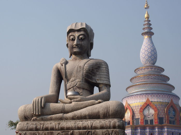 Low angle view of buddha statue by temple against clear sky