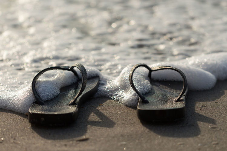 Close-up of shoes on sand at beach