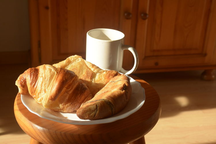 Close-up of croissant and coffee on stool at home