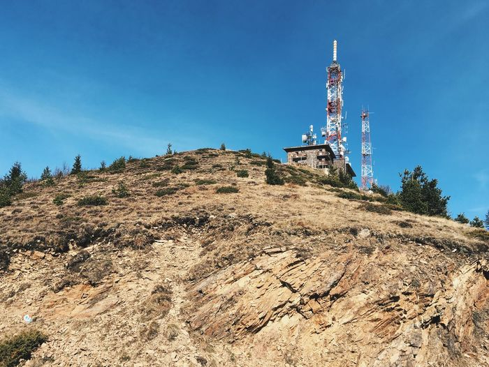 Low angle view of repeater towers on mountain against sky