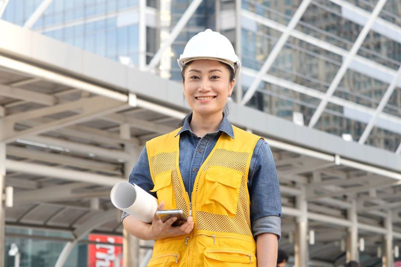 Portrait of mid adult woman holding mobile phone and blueprint while standing against building