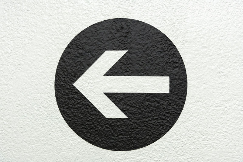 Close-up of arrow symbol on road sign