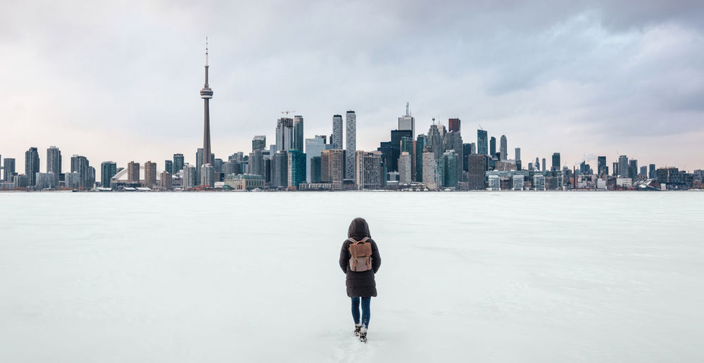 Rear view of woman walking on frozen lake ontario with financial district in background