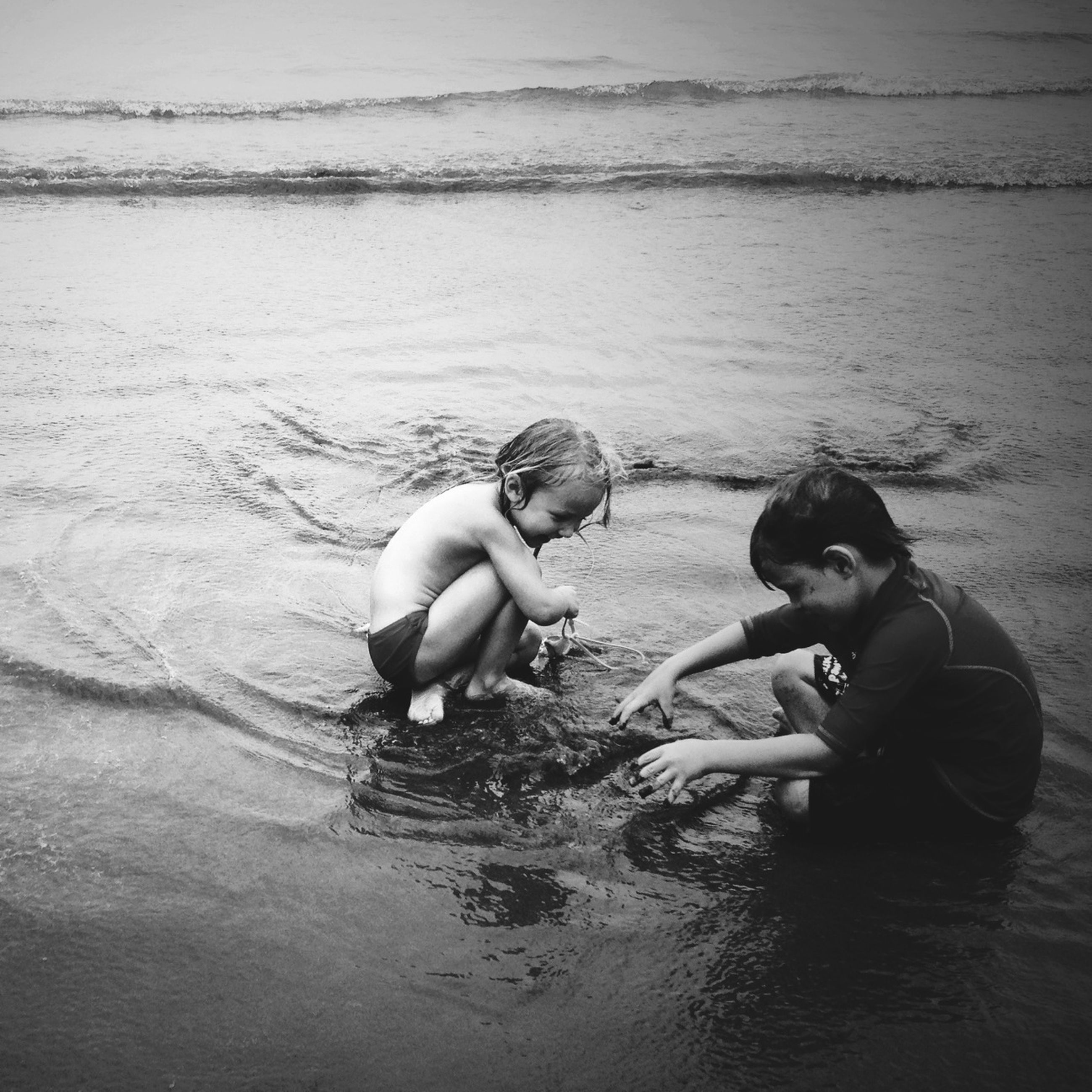 water, lifestyles, childhood, leisure activity, sea, beach, togetherness, lake, boys, nature, swimming, shore, full length, sitting, girls, day, elementary age, high angle view