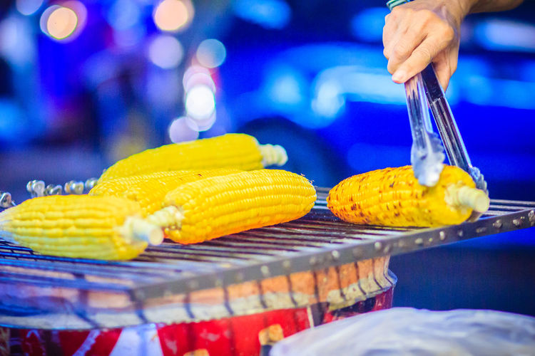 Close up hand of street food vendor while grilling for mixed sweet corn butter. Cook is grilling and sprinkling salt, sugar and butter to the grilled sweet corn on the electric stove. Grilled Corn Khao San Rd Khao San Road KhaoSan Khaosan Rd. Khaosandroad Close-up Corn Focus On Foreground Food Food And Drink Fork Freshness Hand Healthy Eating Human Body Part Human Hand Indoors  Khao San Khao San Knok Wua Khao San Rd. Khaosan Road Khaosanroad Kitchen Utensil Night Market Night Market In Thailand One Person Preparation  Preparing Food Real People Selective Focus Sprinkling Salt Sweetcorn Unrecognizable Person Vegetable