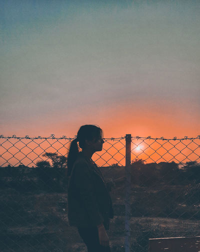 Side view of woman standing by chainlink fence against sky during sunset