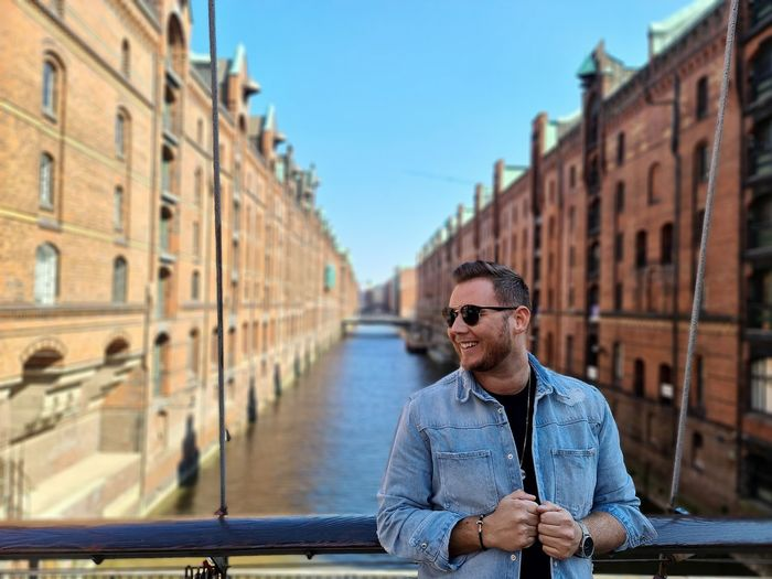 Man wearing sunglasses standing by railing over canal in city