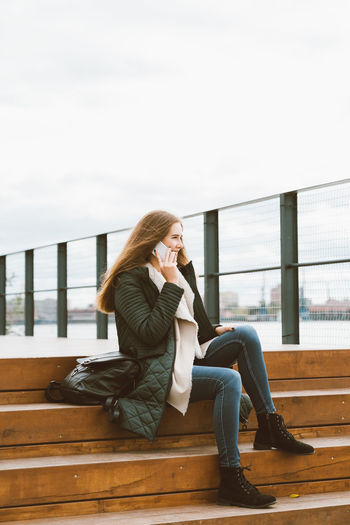 Young woman using mobile phone while sitting on seat against sky