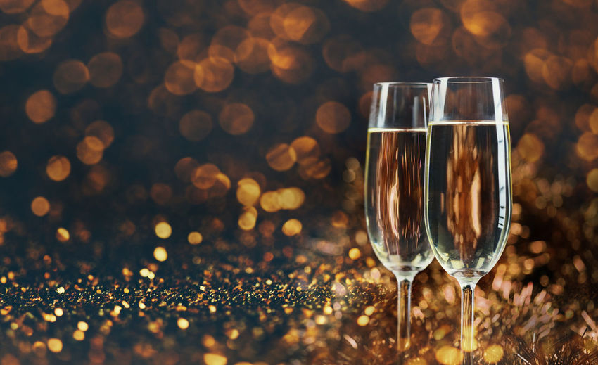 Close-up of champagne flutes on glitters