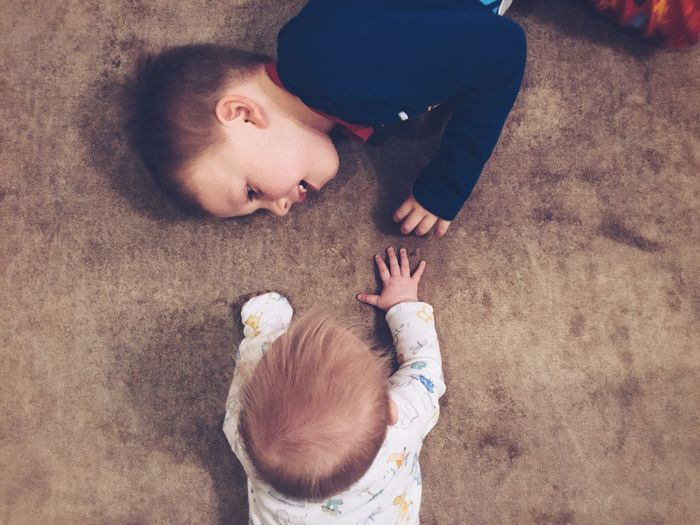 High Angle View Of Sibling Playing At Home