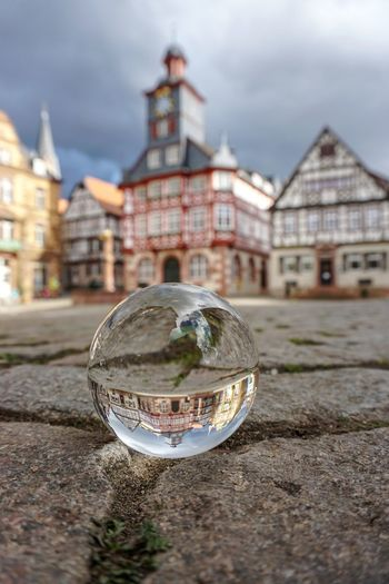 Close-up of crystal ball on glass against building in city