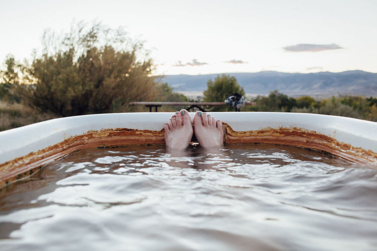 Low section of person relaxing in swimming pool